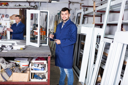 Two smiling cheerful careful workmen inspecting PVC manufacturing output in workshop