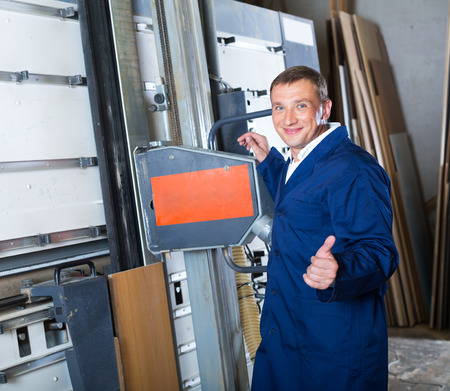 friendly smiling man in workwear cutting plywood using electric saw machinery