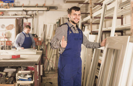 Adult production workers in coverall with different PVC windows and doors Stock Photo