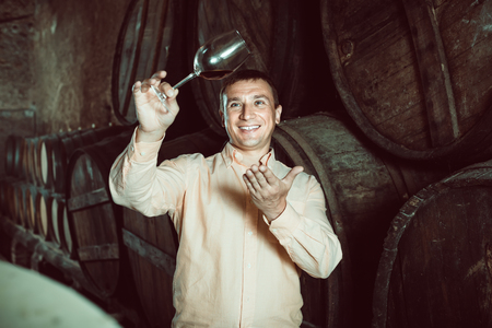 cheerful smiling man looking on glass of wine in winery cellar Stock Photo