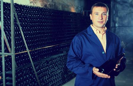 Glad male winery technician posing with bottle of wine in cellar