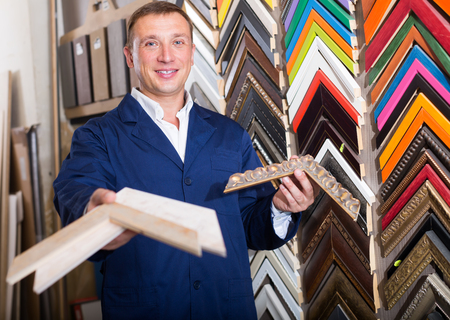 man seller standing in picture framing studio with wooden details