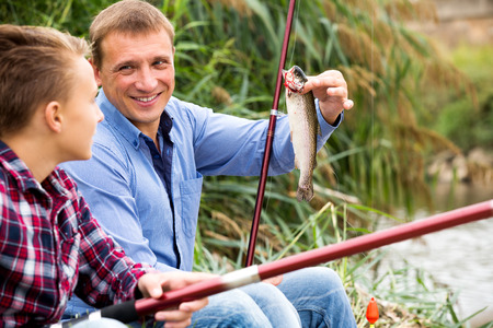 Portrait cheerful man with teenager boy standing together and showing catch fish Stock Photo