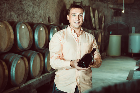Cheerful friendly smiling owner  of winery showing bottle of wine in factory cellar