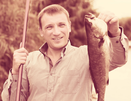 Glad man holding fish after fishing on the river side