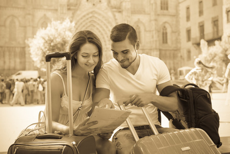 Smiling couple with luggage reading the map at street in sunny day Stock Photo