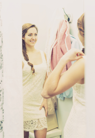 Portrait of happy female with new garment at fitting-room