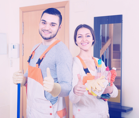 Portrait of smiling professional cleaners with equipment at door of client house