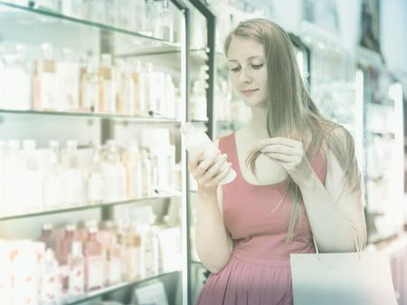 Glad blonde woman take a choise shampoo in perfume supermarke