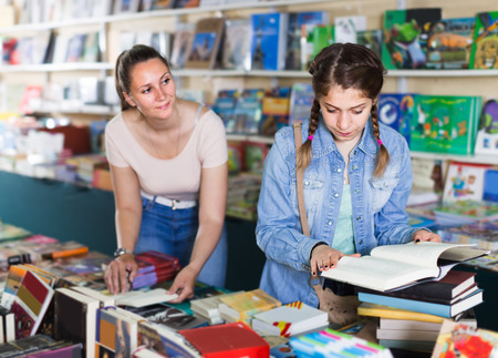 joyous woman showing open book to girl in school age in book boutique Foto de archivo