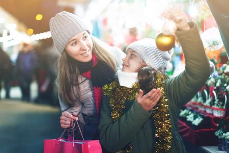 Frau und ihre Tochter bereiten sich für Weihnachten und stellt Bälle am Baum im Freien Standard-Bild - 95409099