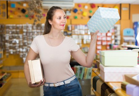 Woman choosing other gift boxes at shop and smiling Stock Photo