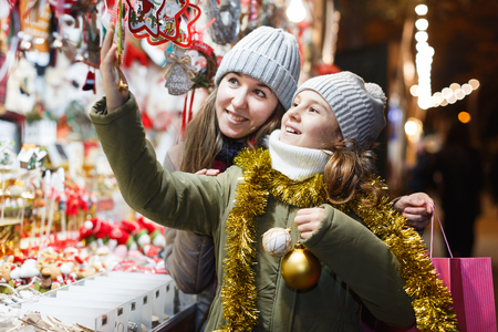 Young girl and her mother are choosing Christmas decorations in the market outdoor.