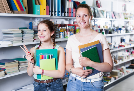 Schoolgirl with mother buying color pencil, markers different color copybook in stationery shop   Stockfoto