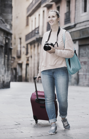 Young girl holding a camera in hands and photographing at a city Stock Photo