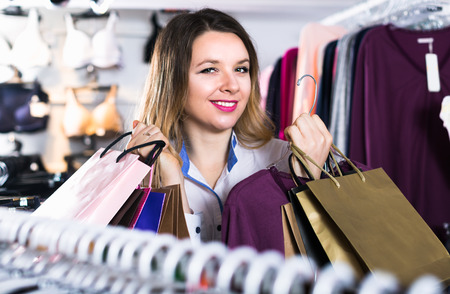 Smiling female customer is enjoying her purchases in wear shop.  Stock Photo