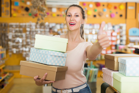 Young  female showing multi colored container at shop   Stock Photo