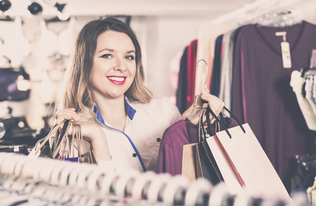 Cheerful  female shopper boasting her purchases in underwear shop