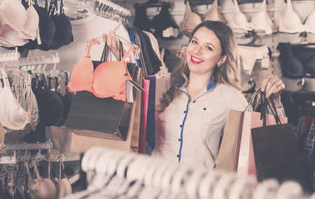 Woman is enjoying her purchases in underwear shop. Stock Photo