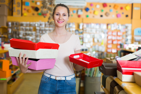 Young woman shows bright boxes for gifts in a store