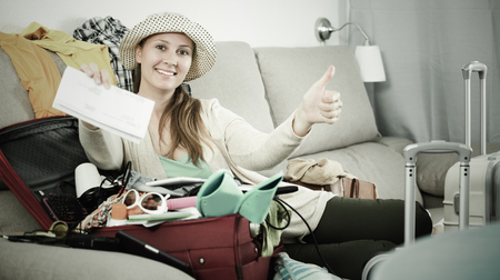 Young smiling woman packing luggage for holidays indoors