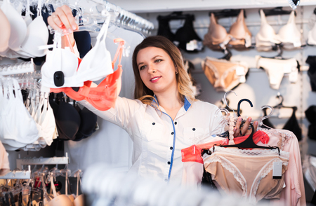 Young woman choosing pretty clothing in underwear shop Stock Photo
