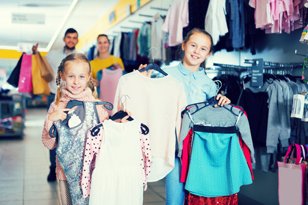 Two sisters with parents satisfied with purchases in children clothing shop