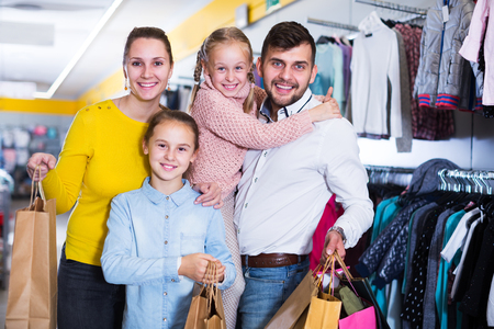 Young positive family with two daughters after shopping in store Stockfoto
