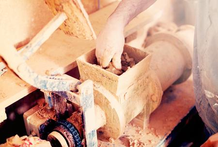Closeup view on clay forming machine in ceramics studio