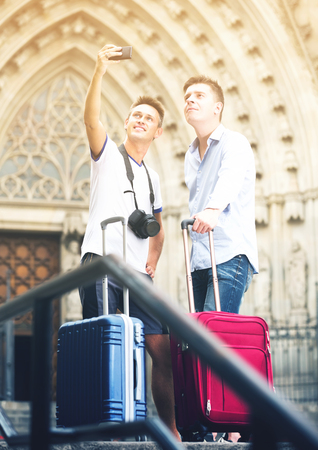 male travelers walking the city and doing selfie