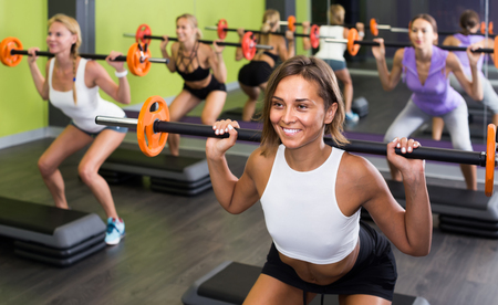 happy germany athletic girls during workout in gym with barbell