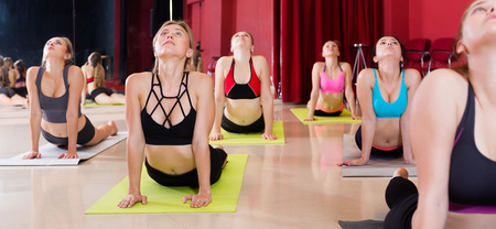 Girls diligently develop flexibility in training on yoga in the room