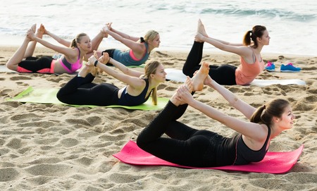 Positive young women training yoga positions on beach in sunny morning  Foto de archivo