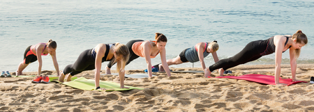 Group of  pleasant friendly females performing yoga on sunny seaside
