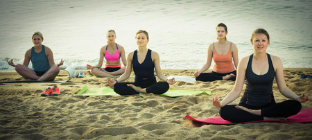 Young women making yoga meditation in lotus pose on sunny beach by ocean