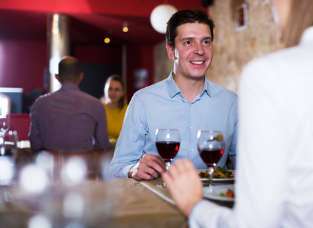 Young man with girlfriend enjoying dinner at comfortable restaurant
