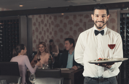 Adult bearded waiter with serving tray welcoming to restaurant Stock Photo