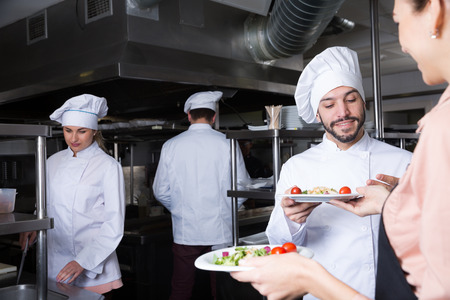 Staff of restaurant with head chef working together in kitchen