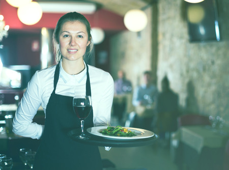 Smiling young woman waitress with serving tray welcoming in restaurant