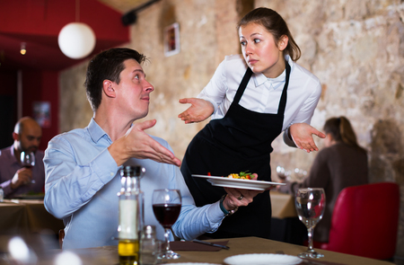 Dissatisfied male expressing displeasure with food talking to excusing waitress in restaurant. Focus on man