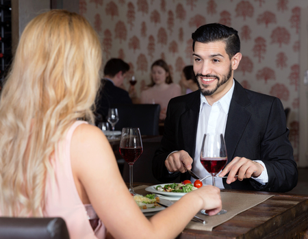 Young happy  handsome man with girlfriend enjoying evening meal in cozy restaurant