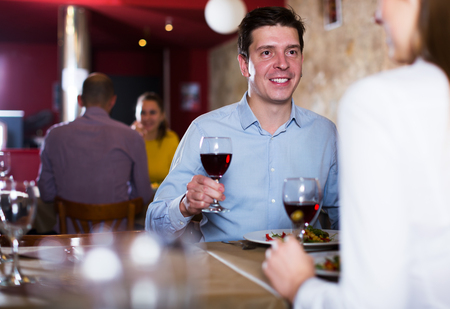 Smiling man with female partner having dinner and drinking red wine at restaurant
