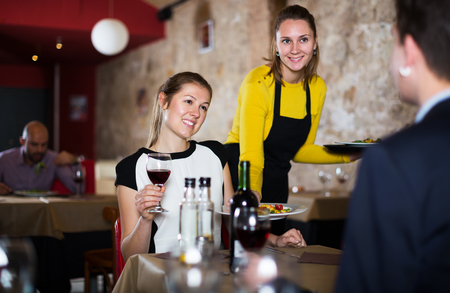 Polite waitress bringing ordered dishes to positive couple at restaurant Stock Photo
