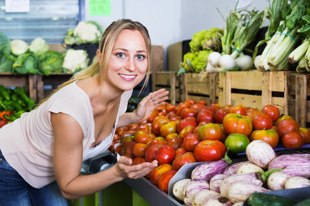 Portrait of young positive cheerful glad woman buying organic tomatoes in shop