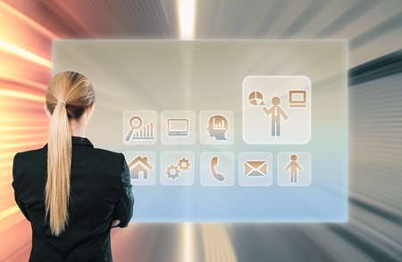 Back view of businesswoman standing in front of virtual screen with icons