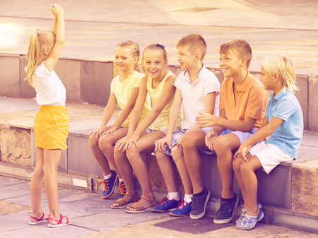 cheerful kids in school age playing charades outdoors Imagens