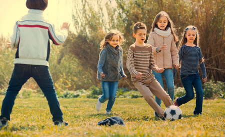 Group of children running after ball on spring  field