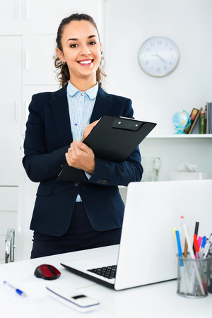 Portrait of happy  positive businesswoman with clip pad in modern office Stock Photo