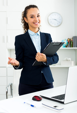 Happy business lady with pad standing near office desk