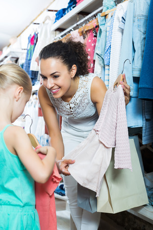 Positive adult mother with daughter buying pink dress in pink color in shop Stock Photo